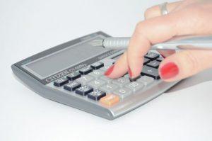 Hand, die einen Stift hält, während sie etwas in einen Taschenrechner tippt
