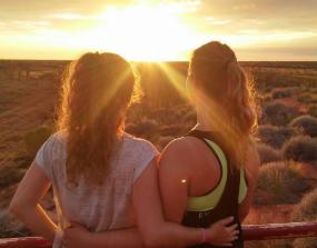 Zwei Au-Pairs betrachten Arm in Arm den Sonnenuntergang in Australien