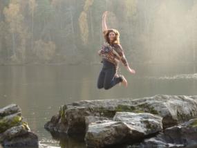 Au-Pair springt auf einem Felsen vor einem See