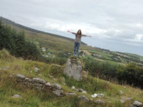Ein Au-Pair steht auf mit ausgestreckten Armen auf einem Felsen mitten in der irischen Natur