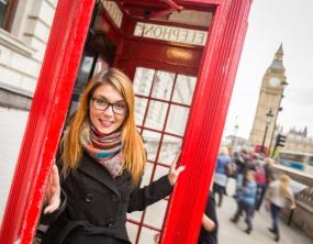Au-Pair in einer roten Telefonzelle. Im Hintergrund Big Ben.
