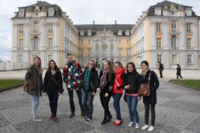 Eine Gruppe junger Menschen vor einem gelben Schloss.