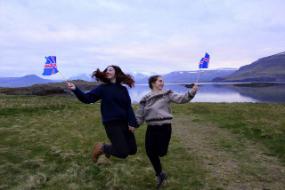 Zwei Au-Pairs in Island hüpfen hoch und halten Island Flaggen in ihren Händen