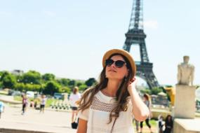 Au-Pair mit Sonnenbrille und Hut vor dem Eiffelturm