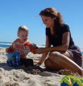 Au-Pair mit Kleinkind am Strand