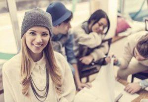 Au-Pair lächelt in die Kamera. Im Hintergrund arbeiten drei ihrer Freunde.