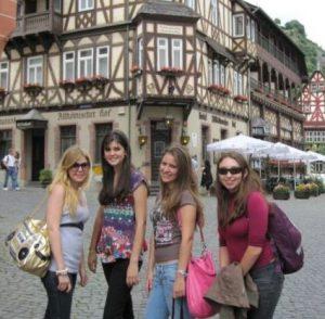 Vier Au-Pairs vor einem typisch deutschen Fachwerkhaus