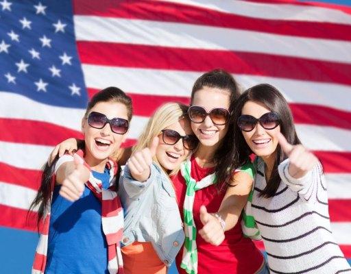 Vier Au-Pairs vor einer amerikanischen Flagge. Sie tragen Sonnenbrillen, lachen und zeigen mit ihrem Daumen nach oben.