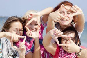 Vier Au-Pairs, die ihre Zeigefinger und Daumen so zusammenpressen, als wollten sie ein Foto machen